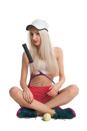 Beautiful girl sitting in a red skirt with a tennis racket and ball on a white background